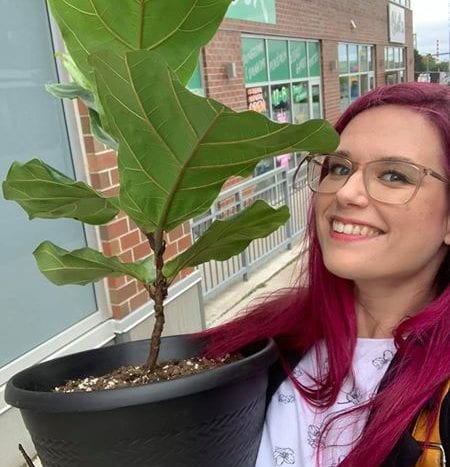 Lacey holds a Fiddle Leaf Fig Plant in her arms with a big smile on her face while standing in front of Bloom 24 Floristry in Halifax.